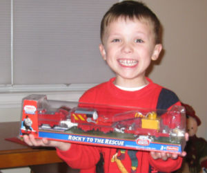 Adam holding trackmaster Rocky to the Rescue