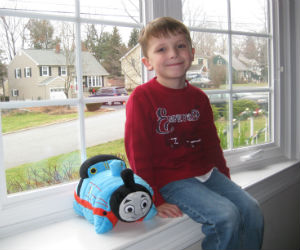 Adam proudly enjoying is Thomas pillow pet