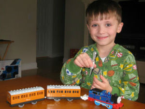 Thomas adding water to his Thomas steam train